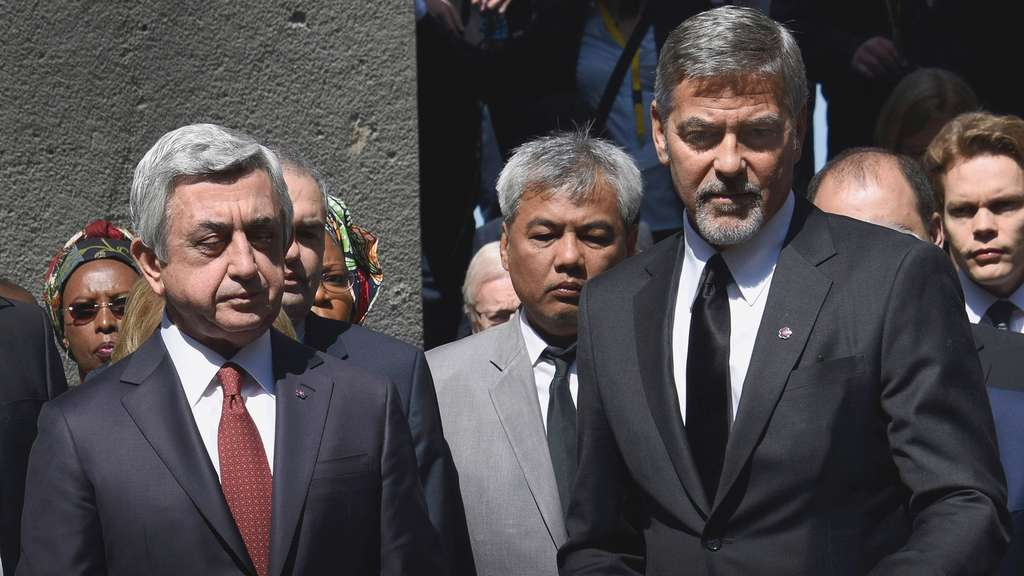 US actor George Clooney (R) and Armenian President Serzh Sarkisian lay flovers at the Genocide Memorial in Yerevan on April 24, 2016.Hollywood star and rights advocate George Clooney led thousands of Armenians on a march to a hilltop memorial in Yerevan to commemorate the 101st anniversary of the WW I-era Armenian genocide in the Ottoman Empire. / AFP PHOTO / KAREN MINASYAN