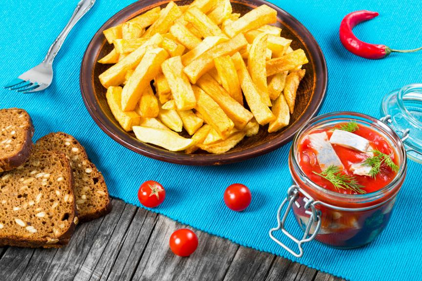 Potato Fries with pieces of chili pepper on the white dish and Slices of marinated Norwegian herring in tomato sauce on the pieces of rye bread, the glass jar with delicious herring with dill, top view (myViewPoint)